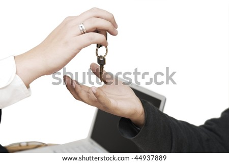 Handing keys with a computer on the background - stock photo