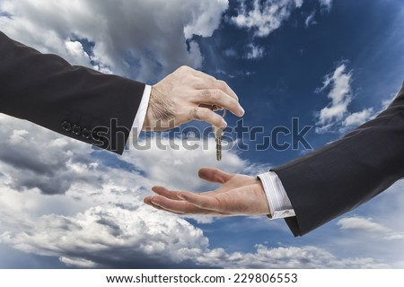Handing over house keys on dramatic sky background with clouds. - stock photo