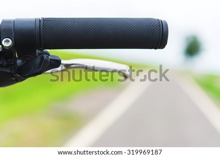 handlebar of a bicycle with bicycle lanes at parks - stock photo
