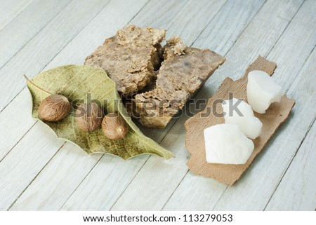 handmade african black soap and ingredients, shea butter nuts, leaves and white shea butter - stock photo
