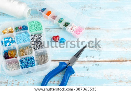 Handmade background with copy space. Box with beads, spool of thread, pliers and glass hearts to create hand made jewelry on old wooden background. Handmade accessories and tools - stock photo