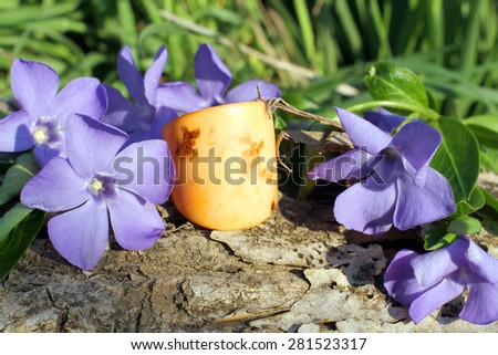 Handmade bone yellow ring with wood violet in spring on the nature background - stock photo