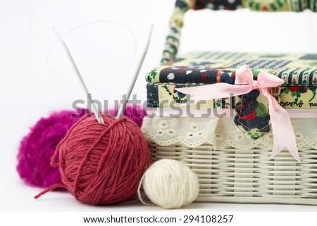 Handmade box for knitting, pink, white woolen yarn balls and knitting needles on white background - stock photo