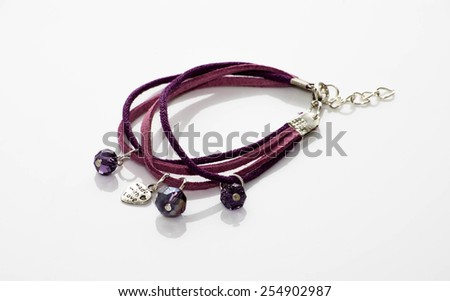 Handmade bracelet with leather straps, metal heart and purple crystals isolated on white background - stock photo
