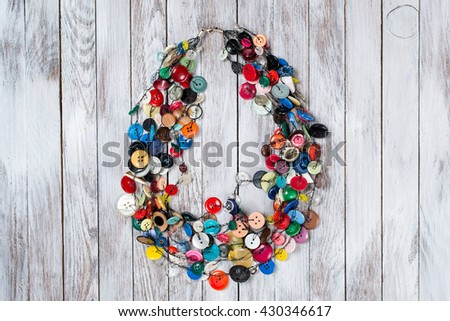 Handmade bright colored jewelry made of plastic buttons on white wooden background. - stock photo