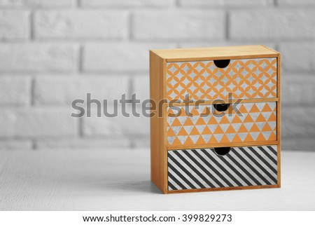 Handmade chest of drawers for jewelry on wooden table against wall background - stock photo