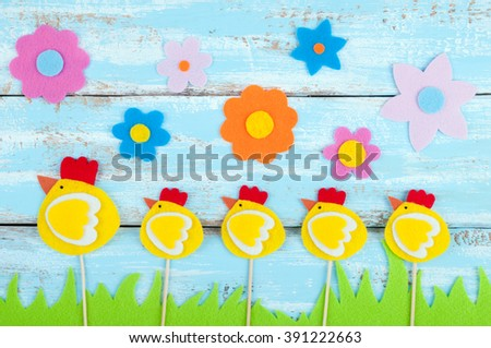 Handmade chickens, grass and flowers made of felt on wooden rustic background. Children's handmade Easter card. Top view - stock photo