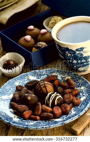 Handmade chocolate candies with cup of tea, cocoa beans, blue gift box on the vintage wooden table - stock photo