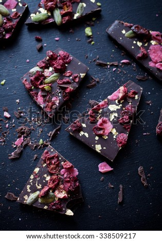 Handmade chocolate with berries, pistachios and edible gold - stock photo