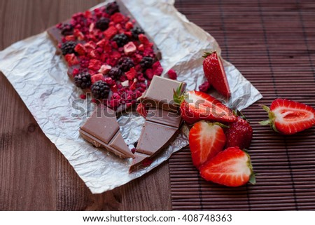 Handmade chocolate with fresh and dried berries, raspberries, strawberries, black currants, blackberries, cocoa powder, on wooden background in rustic style - stock photo