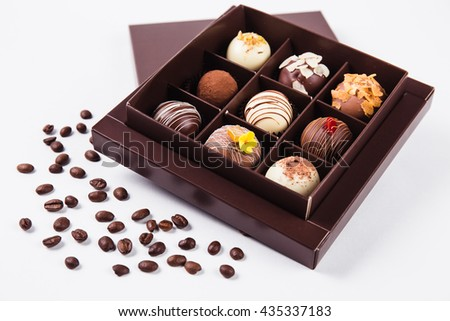 handmade chocolates in a square box and coffee beans near (top view) - stock photo
