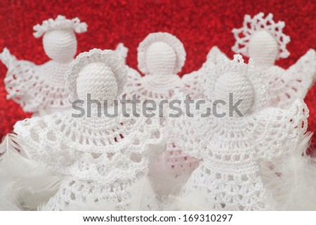 Handmade Christmas Crochet Angels on red - stock photo