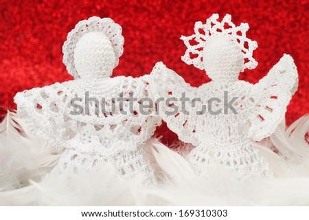Handmade Christmas Crochet Angels on red - stock photo