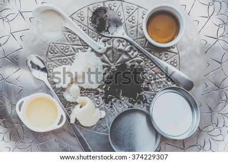 Handmade cosmetic ingredients - coconut and shea tree butter, olive oil, round coffee and sugar. Organic scrub and body cream. Toned picture - stock photo