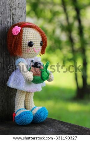 handmade crochet girl and parrot doll on green background - stock photo