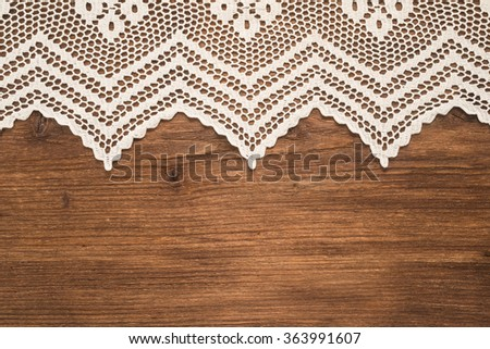 Handmade crochet tablecloth pattern over wooden background - stock photo
