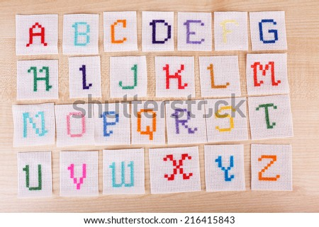 Handmade embroidered letters on white fabric, on wooden background - stock photo