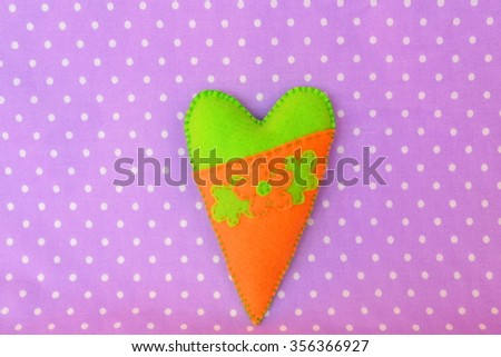 Handmade felt heart - symbol of Valentines Day, on violet background, with place for text  - stock photo