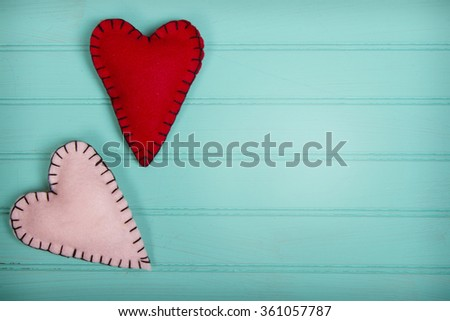 Handmade felt hearts with black stitching on a turquoise blue panel background - stock photo