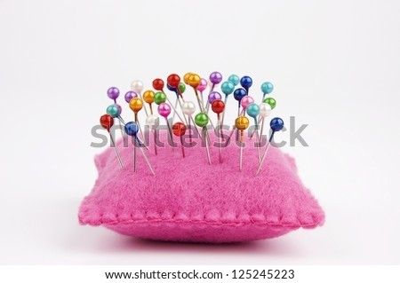 Handmade felt pin cushion with multicolored sewing pins stuck in - stock photo