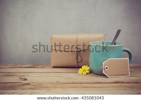 Handmade gift box and coffee cup on wooden rustic table.  - stock photo