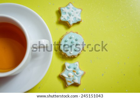 Handmade ginger cookies and cup of tea on green background - stock photo