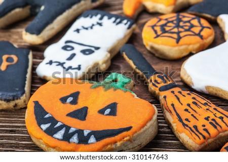 Handmade Halloween cookies on a wooden table. focus on pumpkin - stock photo