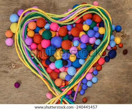 Handmade heart made with multicolored hand felted beads and laces - stock photo