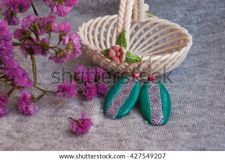 Handmade jewelry, green earrings, interesting, made of polymer clay, african style. Still life with earrings, pink flowers and ceramic vase. - stock photo