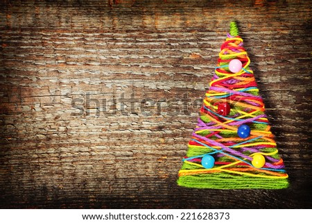 Handmade knitted Christmas tree on old wooden background. Image with retro filter effect - stock photo