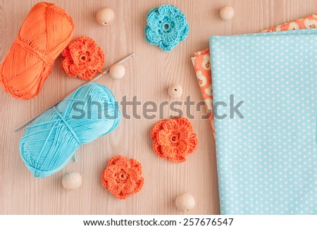 Handmade knitted crochet flowers and wood beads. Cotton textile for needlework. Top view - stock photo