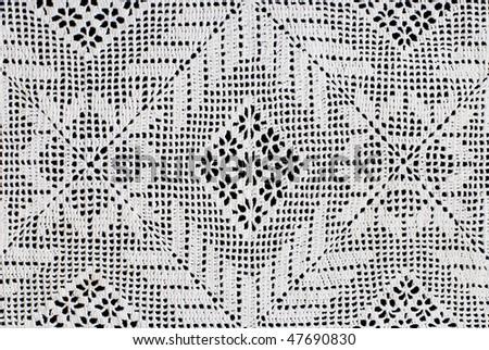 Handmade lace doily on a black background - stock photo