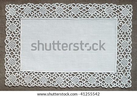 Handmade lace doily on linen - stock photo
