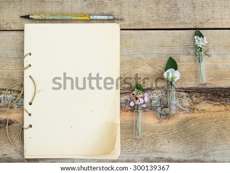 handmade notebook with old pen and small bouquet of wildflowers on a wooden background - stock photo