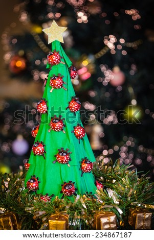 Handmade paper christmas tree with chocolate ladybirds in front of a real christmas tree - stock photo