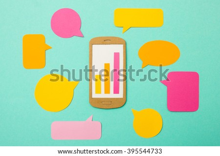 Handmade paper model of smart phone with growth chart and speech bubbles - useful image for mobile marketing, mobile commerce or advertising - stock photo