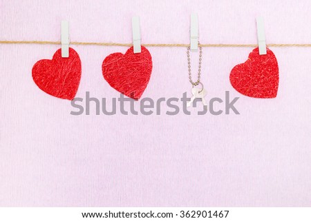 Handmade red hearts and keys hang on white clothespins over pink background - stock photo