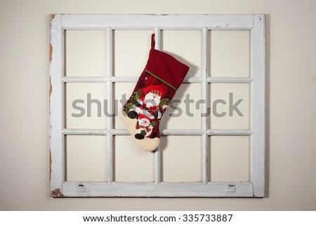 Handmade Santa boot hang on a rustic window frame - stock photo