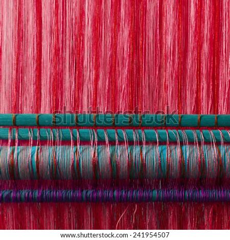 Handmade silk textile industry, silk scarf on a old machine (Vietnam), red - stock photo