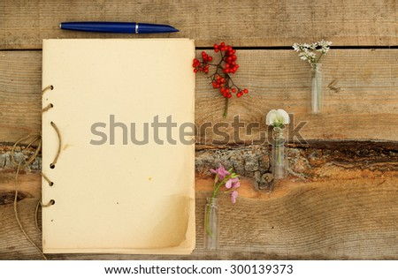 handmade sketchbook with pen and small bouquet of wildflowers on a wooden background - stock photo