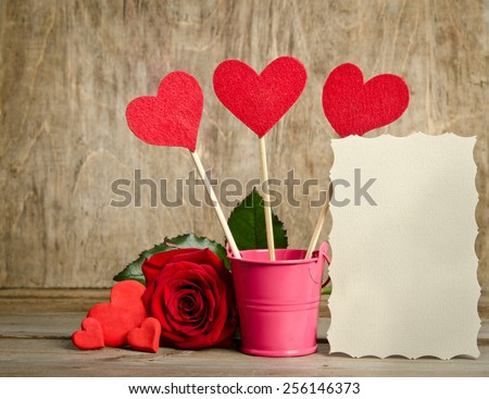 handmade skewers  with cloth hearts are standing in the metal bucket near blank for you text and  beauty red rose is lie near handmade hearts on wooden background - stock photo