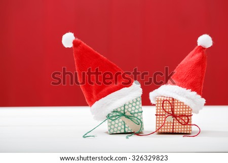 Handmade small gift boxes with Santa hats on red wooden wall - stock photo