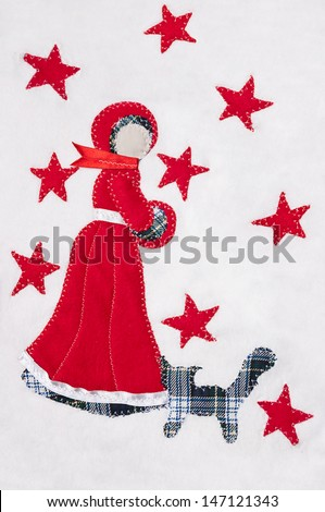 Handmade snow maiden stitched on a white fluffy background with red stars and pattern cat. With copy space. - stock photo