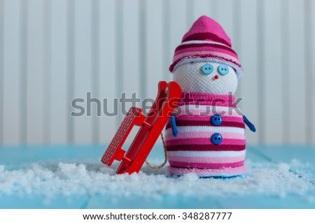 Handmade snowman in marsala color sweater with red sled on snow in winter. Christmas postcard background with empty space. - stock photo