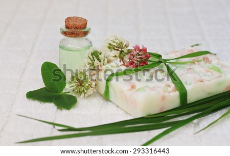 Handmade soap bar aromatherapy oils herbal cosmetics scented clover flower fresh green leaves, relaxing bathroom care set - stock photo