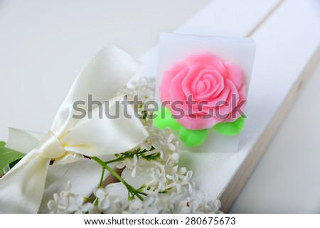 Handmade soap. Cake in the shape of flowers and roses. The branch of white lilac with satin ribbon - stock photo