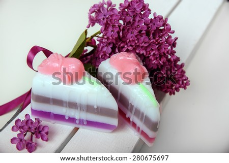 Handmade soap. In the form of a piece of cake. The branch of lilac with a satin ribbon - stock photo