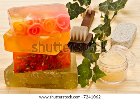 Handmade soaps and bath items on bamboo board with ivy branch - stock photo
