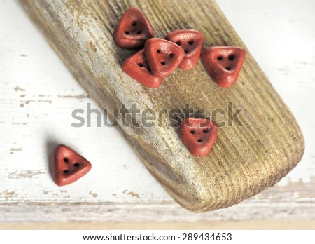 Handmade Triangle Buttons On Aged Wooden Board, Wabi-sabi Style Still Life - stock photo