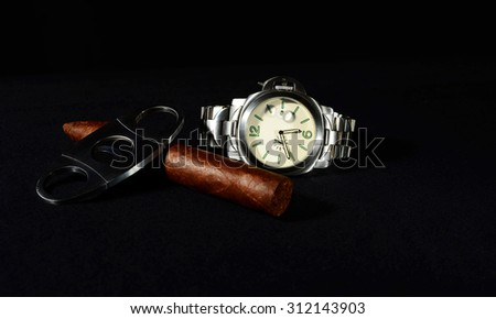 Handrolled cuban cigar whit an elegant wristwatch isolated over black background - stock photo